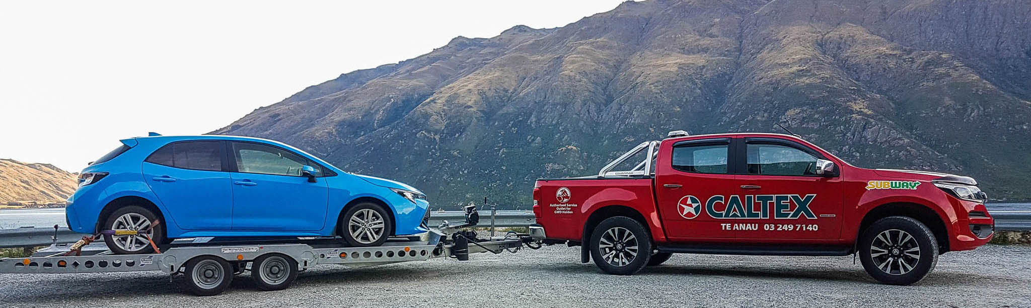 Red salvage truck towing a trailer with a blue vehicle onboard