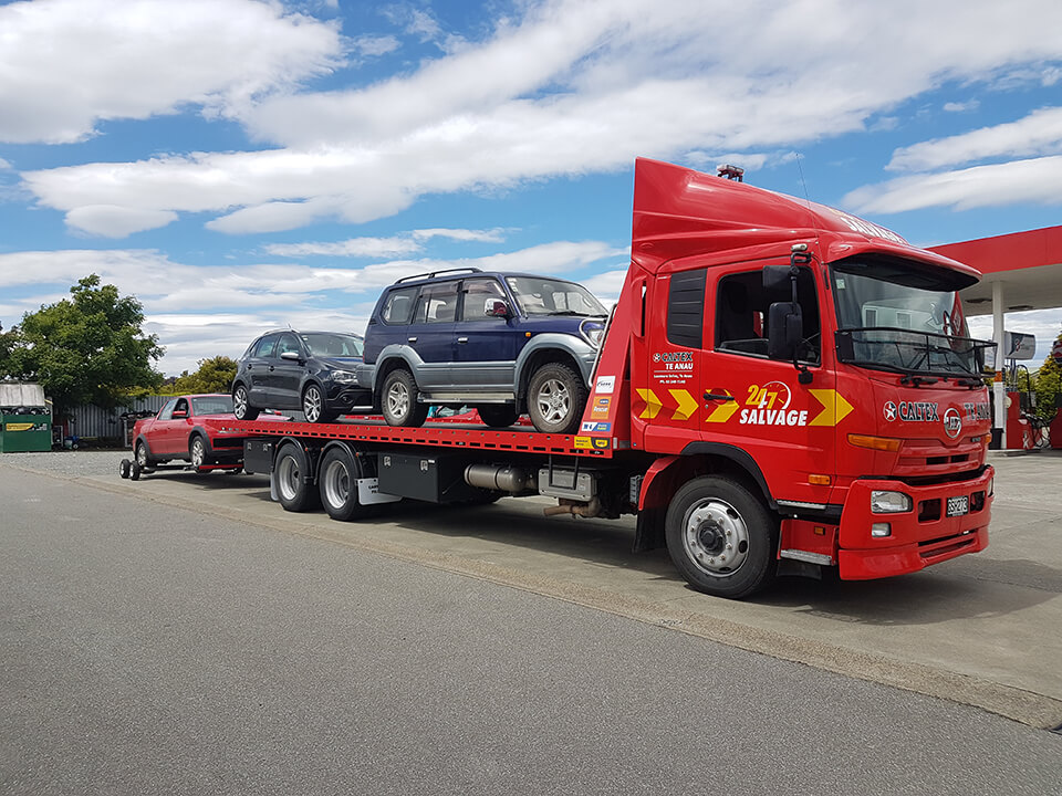 Large red Caltex truck with two vehicles onboard and another vehicle on a trailer